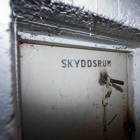 Skyddsrumsdörr omgiven av vitamålade betongväggar samnt ett infällt porträtt på Anders Mellin. En man i 65-årsåldern med mörka glasögonbågar.