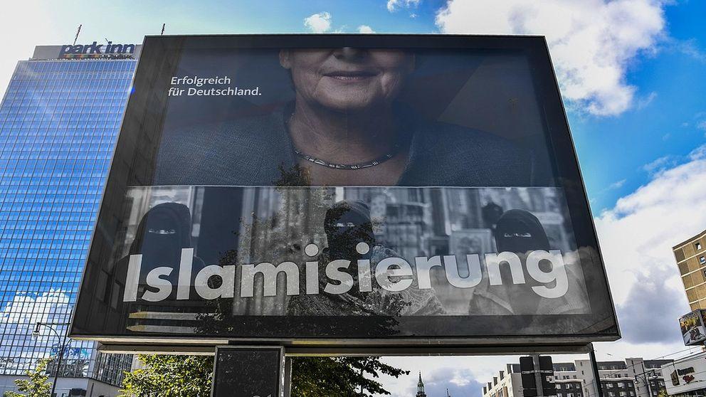 En valaffisch som visar en halv Angela Merkel och ordet islamisering.