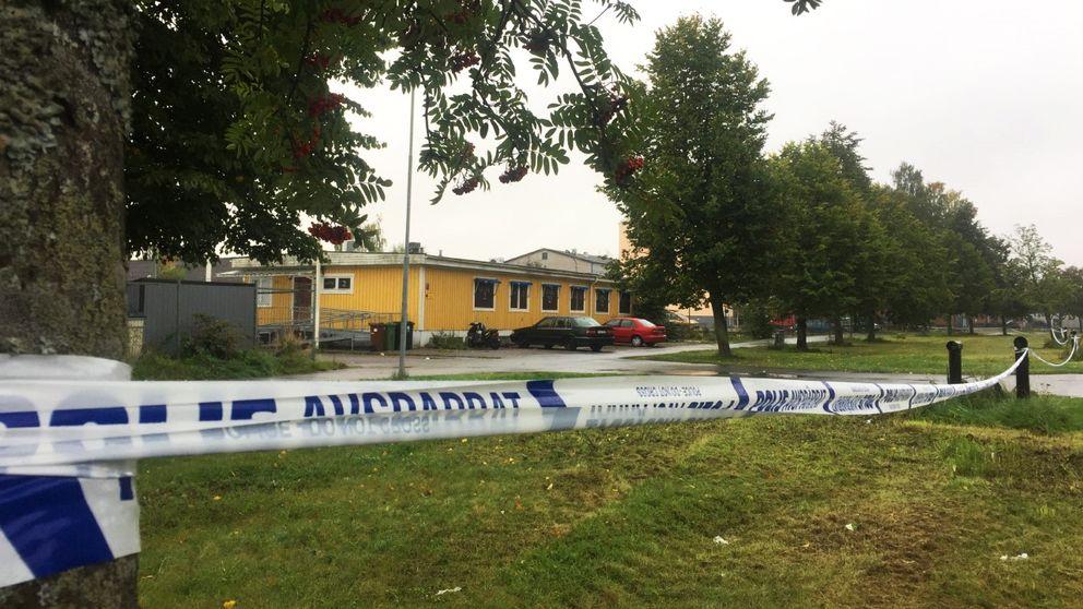Polisavspärrning i förgrunden, gul lokal i bakgrunden