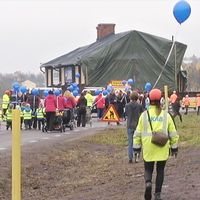 husflytt på väg, många personer som går, flera med ballonger