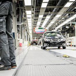 ett par ben i förgrunden och en bil i bakgrunden