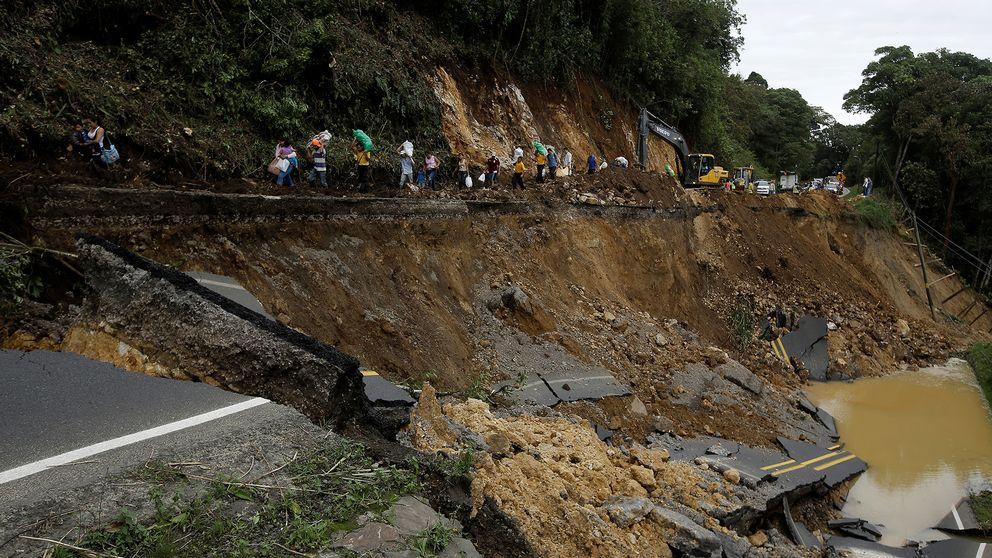Människorna som går längs vägraset i Casa Mata, Costa Rica, färdades med buss som inte kunde ta sig längre när vägen rasade, orsakat av stormen Nate.