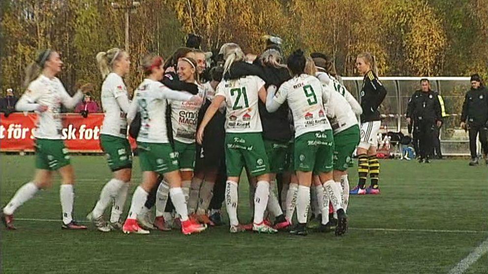 kvinnliga fotbollsspelare samlas i en ring på plan