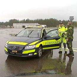 Två män står utanför en bil på F21 i Luleå.