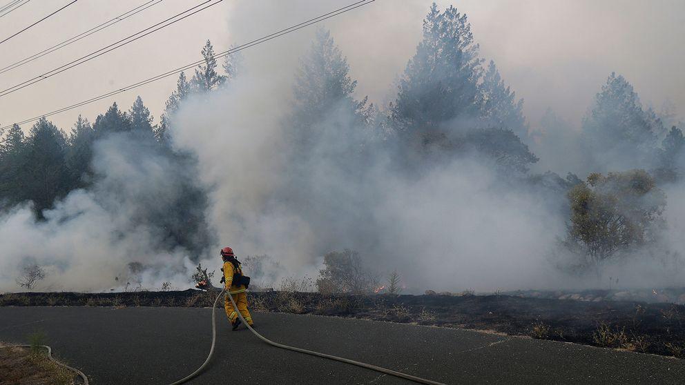 En brandman jobbar med att släcka branden i närheten av Oakmont i Santa Rosa, Kalfornien.