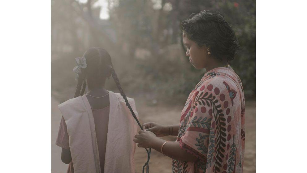 En mamma flätar sin dotters hår inför skoldagen