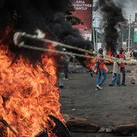 Oppositionsanhängare blockerar gator och bränner bildäck i Kisumu, Kenya.