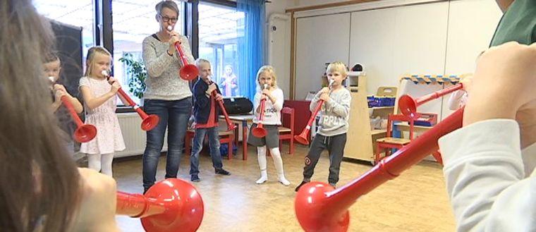 Barn och förskolepedagog spelar blåsinstrumentet pbuzz.