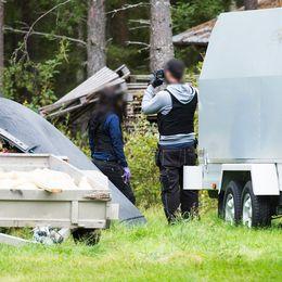 två poliser på en gård, släpvagnar och en traktor syns