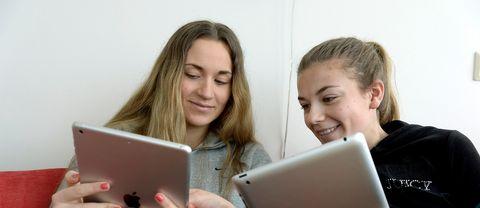 Två unga tjejer sitter med läsplattor.