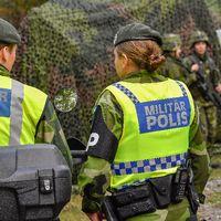 Två kvinnliga militärpoliser framför ett förband med soldater och ett kamoflerat militärfordon.