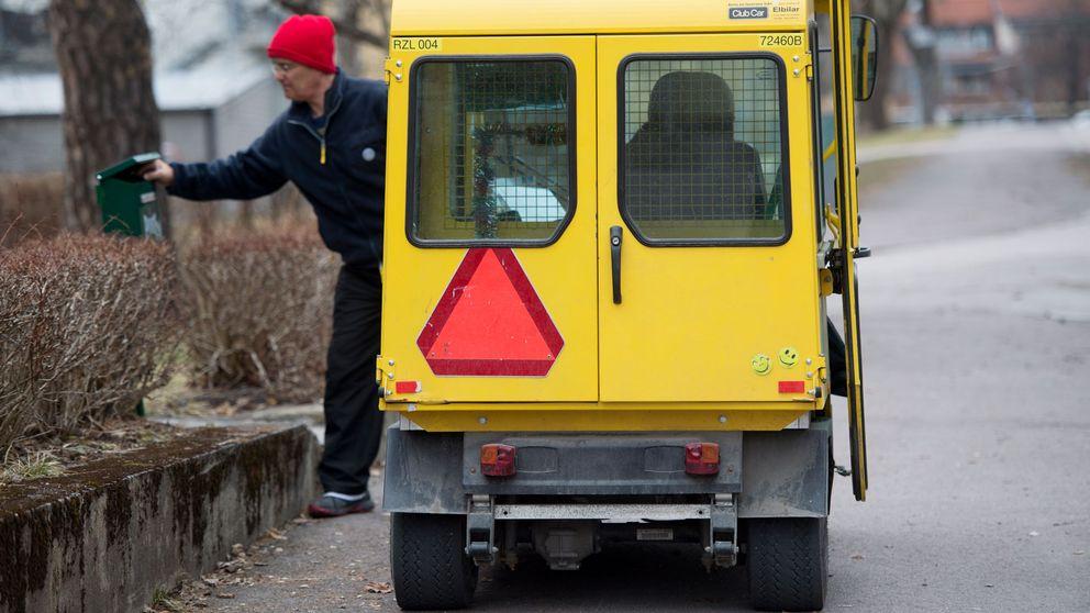 Brevbärare med elbil lägger post på låda.