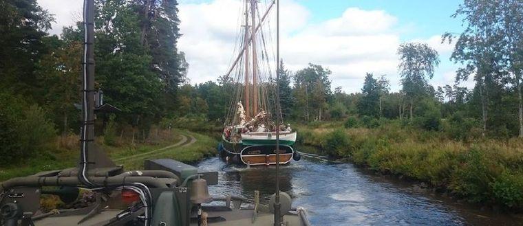 Svallvågor från stridsbåten gjorde att en skonert trycktes upp mot kanalbanken och fastnade med riggen i ett träd.