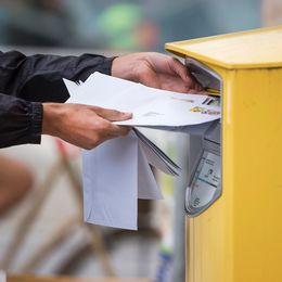 Postar brev i en postlåda.