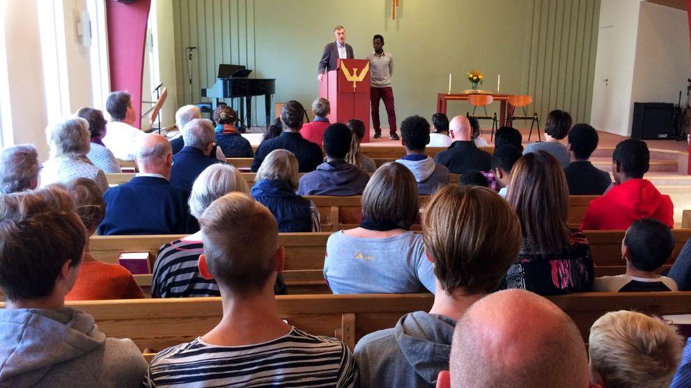 Personer sitter i kyrkan och lyssnar på Leif Olander.