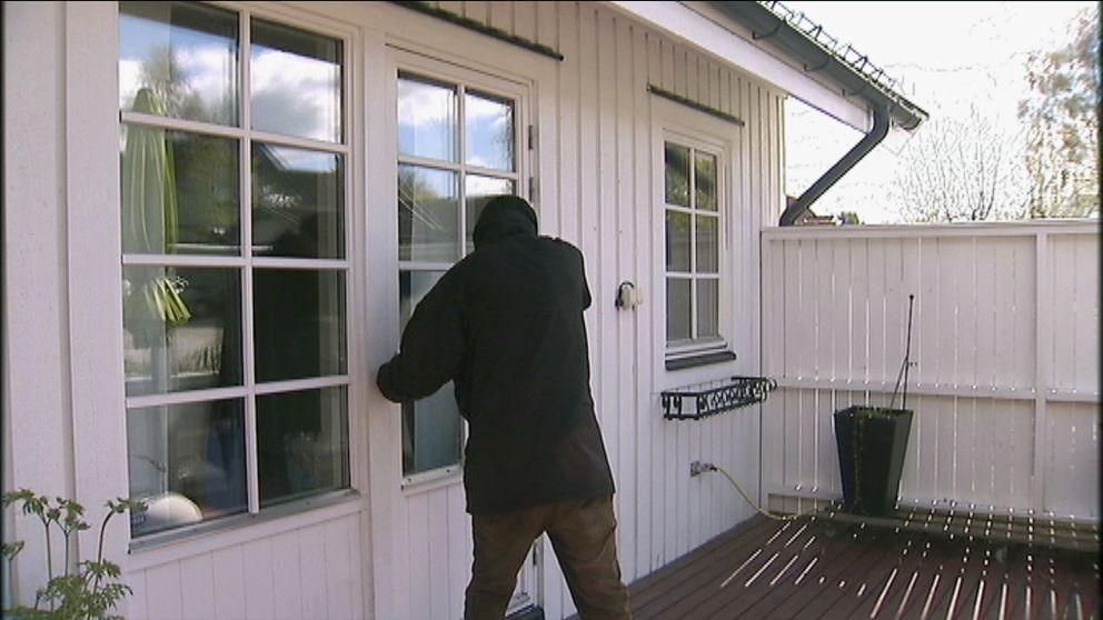 arrangerad bild på person som bryter sig in i villa via altandörr