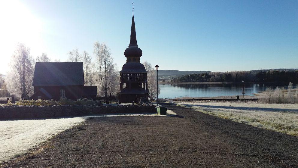 vy över kyrka och spetsigt klocktor, med sjö bakom. Rimfrost och sol