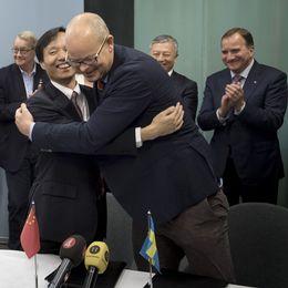 Aries Liu, vd Automative alliance didi och Nevs vd Stefan Tilk kramar artigt varandra vid en presskonferens.