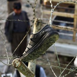 Afghan residents look at victim's footwear hanging on barbed wire outside the Imam Zaman Shiite mosque the day after a suicide attack during Friday evening prayers, in Kabul on October 21, 2017. A strong smell of blood and flesh permeated the Imam Zaman mosque in Kabul on October 21 hours after dozens of Shiite worshippers were slaughtered by a suicide bomber during evening prayers. Broken glass and dust covered the red carpet, soaked in the blood of the men, women and children who had been praying on Friday when the attacker blew himself up, causing carnage in the cavernous prayer hall. / AFP PHOTO / WAKIL KOHSAR