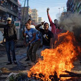 Flera människor står bakom en eld, personen längst fram skriker och håller upp handen i luften.