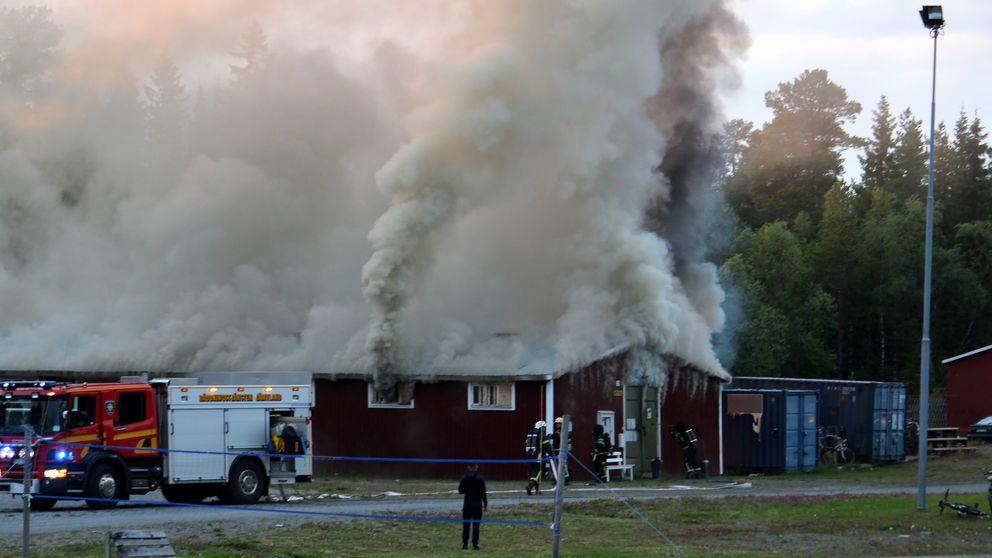 Tjock grå rök väller ut från en röd byggnad. Bilar från räddningstjänsten står bredvid.