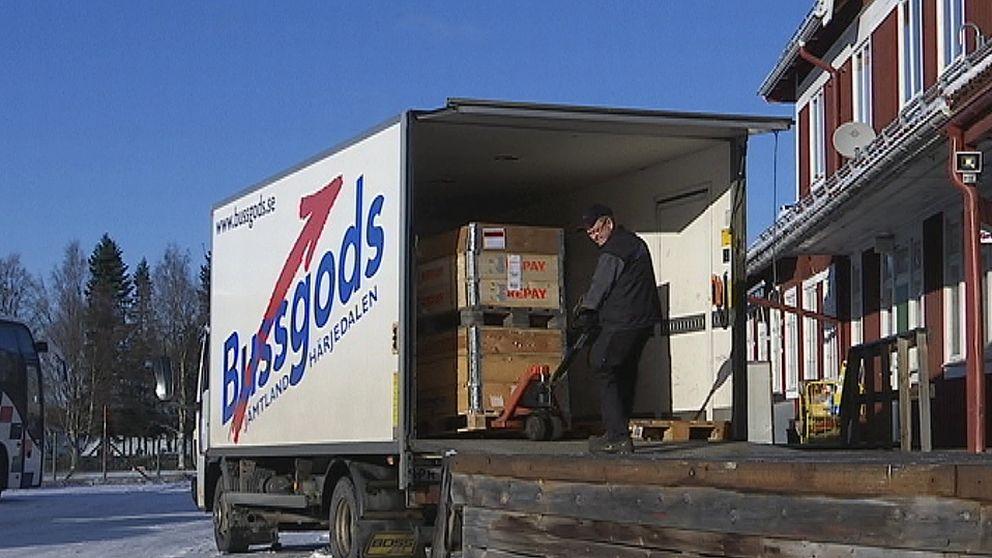 En man lastar av från en vit lastbil där det står Bussgods på sidan.