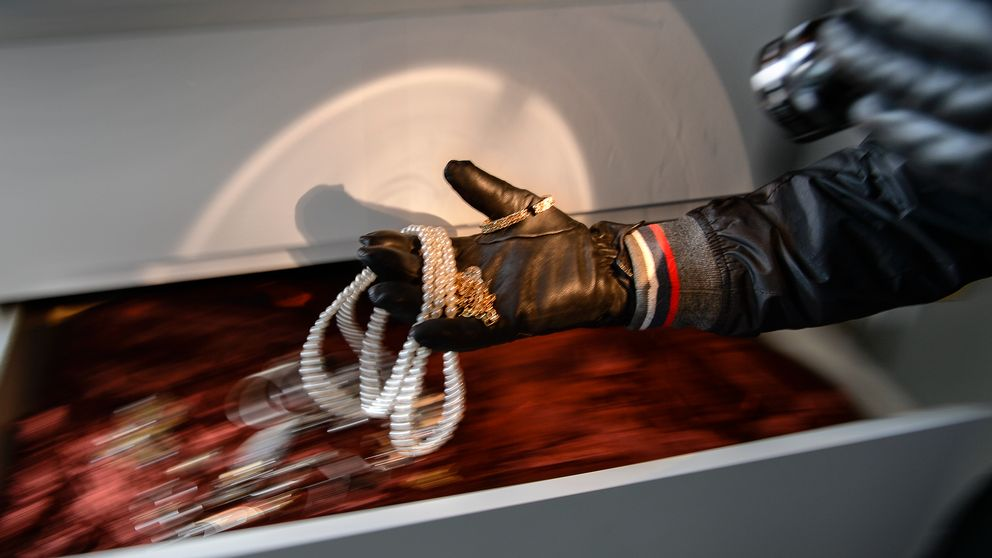 En handskbeklädd person stjäl smycken ur en byrålåda.