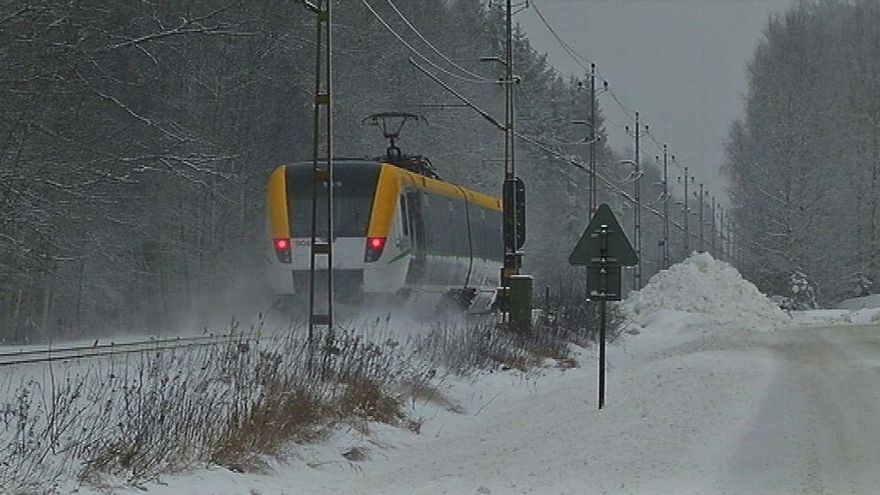 Ett tåg, snön yr bakom det.