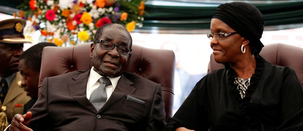 FILE PHOTO: Zimbabwe President Robert Mugabe (L) speaks to his wife Grace during the funeral of his sister, Bridget in the village of Zvimba, Zimbabwe January 21 2014. REUTERS/Philimon Bulawayo/File Photo