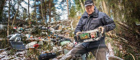 Naturbevakaren Anders Berglund står bland mängderna av sopor som har slängts i naturreservatet. I handen har han lyft upp en gammal dator.
