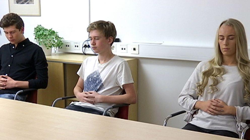 Tre personer sitter och gör andningsövningar.