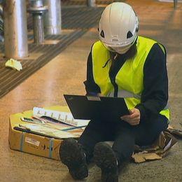 Produktionsstopp på Stora Enso, anställd sitter på golvet med dator.