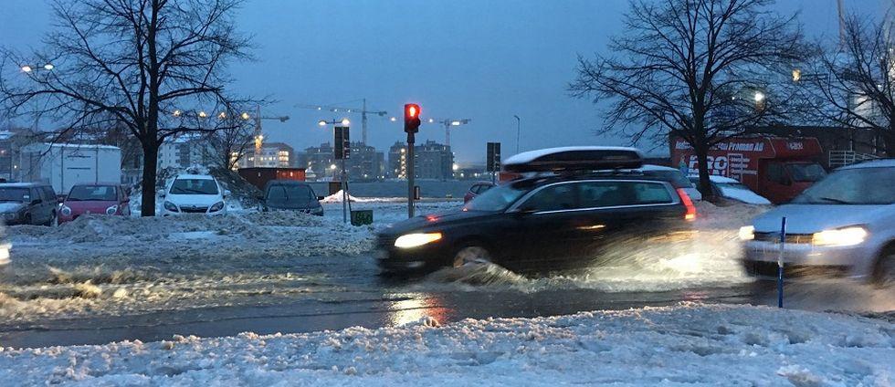 bilar kör i snömodd i stan