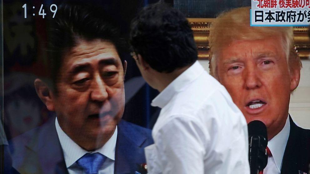 En man framför Shinzo Abe och Donald Trump på skärmar i Tokyo