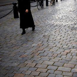 Kvinna går på gatstenar.