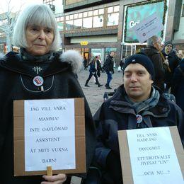 """Birgitta och Erik står med varsin skylt på demonstrationen. """"Jag vill vara mamma, inte oavlönad assistent åt mitt vuxna barn."""" """"Till nyss hade jag trygghet, ett trots allt hyfsat liv. Och nu?"""""""