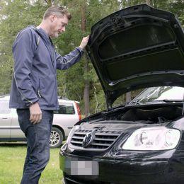 Man står och tittar på motorn till sin bil.