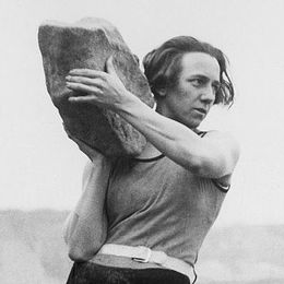 Kvinna håller ett stort stenblock i huvudhöjd, redo att kasta det.
