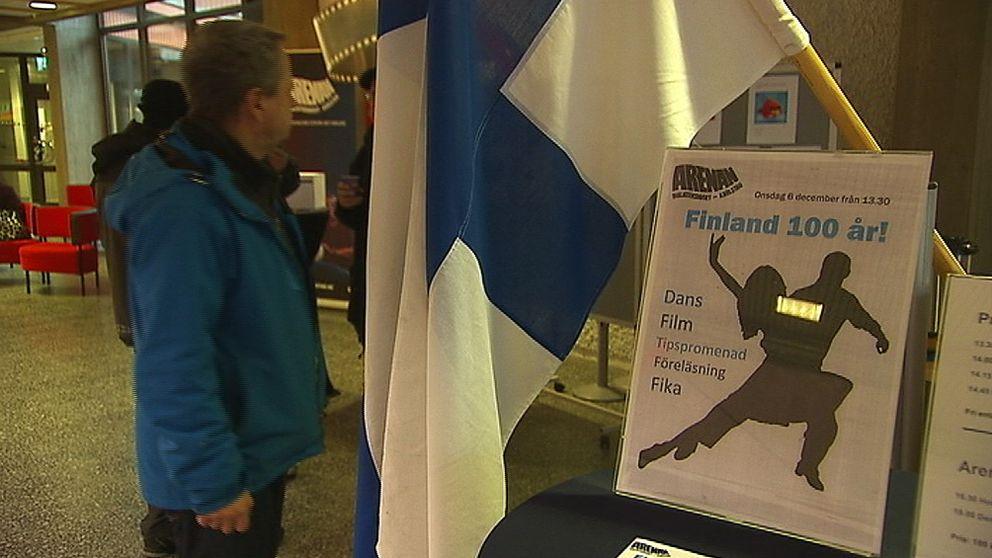 """En finsk flagga, en skylt där det står """"Finland 100 år!"""". En man står bredvid"""