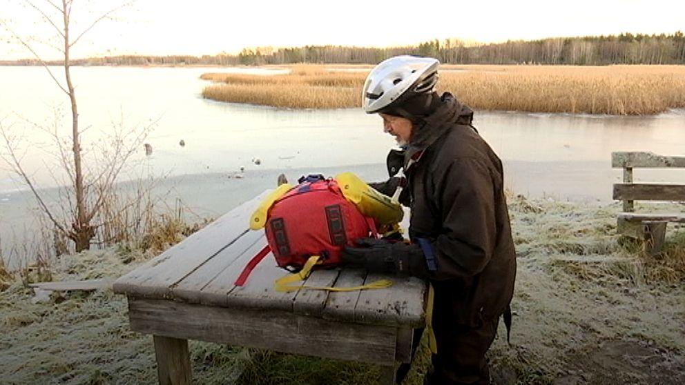 En man med hjälm lägger upp en ryggsäck på ett bord som står utomhus.