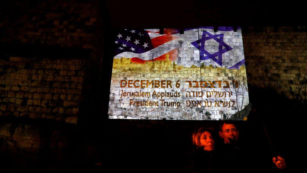 Två personer i Jerusalem framför en projektion med USA:s och Israels flaggor