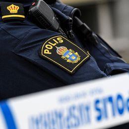 Axeln på en polis, myndighetens symbol syns. Ett avspärrningsband syns i förgrunden