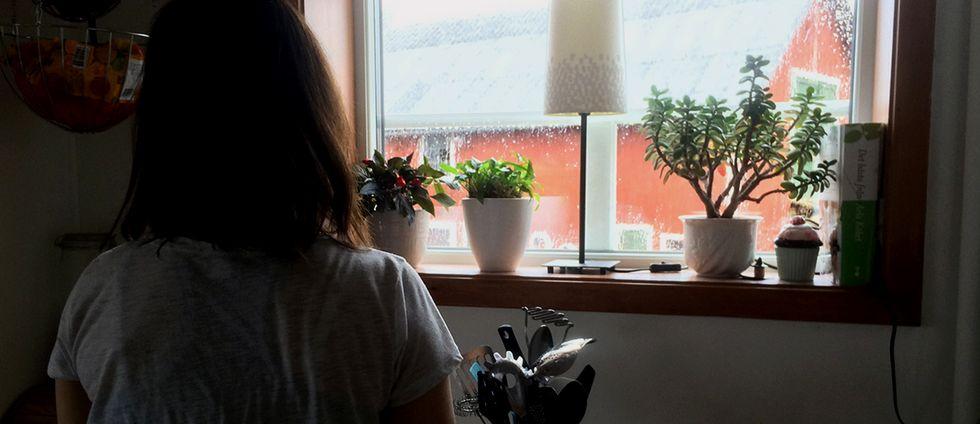 Kvinna står med ryggen mot kameran och tittar ut genom fönstret.