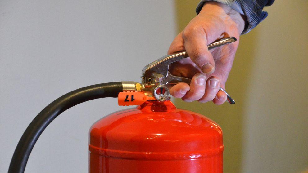 Hand som håller i en brandsläckare.