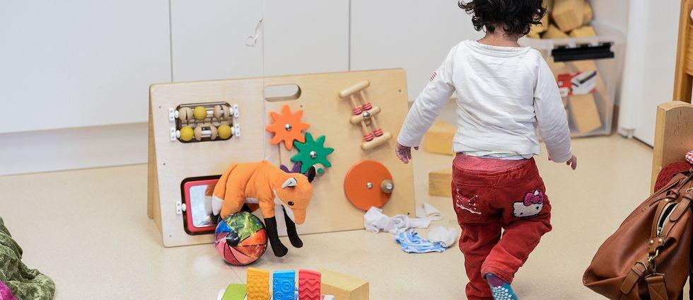 Barn på förskola. Leksaker på golvet.