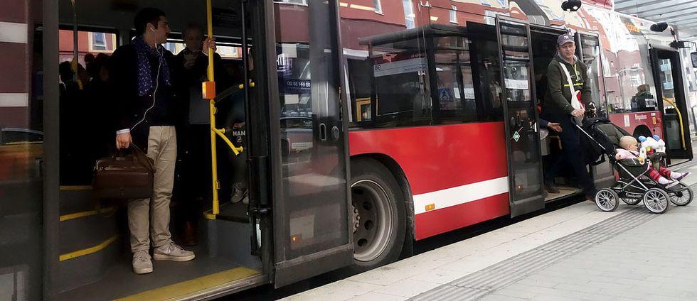 Personer som kliver av en röd buss.