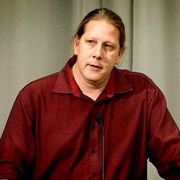 Patrik Liljeglöd (V) står i en talarstol och talar i en mick.