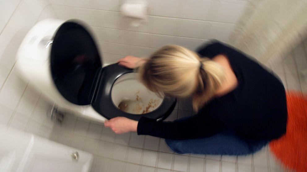 En kvinna spyr i en toalett.