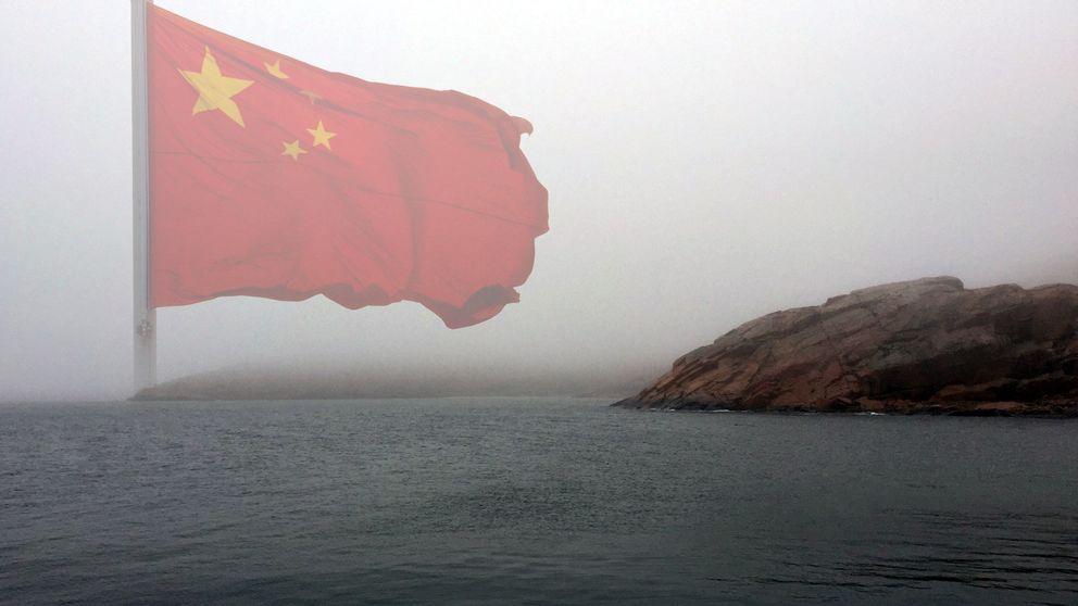 Dimmig bild av kusten intill en kinesisk flagga