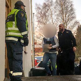 väktare leder in mansperson i byggnad, ansiktet är dolt